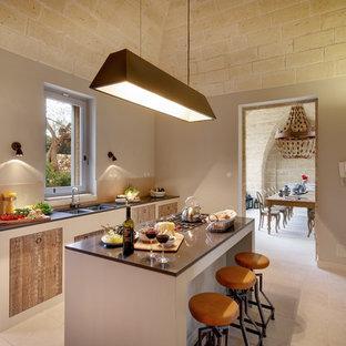 Ispirazione per una cucina parallela mediterranea con lavello a doppia vasca, ante lisce, ante in legno scuro, isola, pavimento beige e top grigio