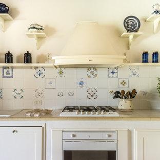 Esempio di una cucina a L mediterranea con lavello da incasso, ante con riquadro incassato, ante bianche, paraspruzzi multicolore, elettrodomestici bianchi e top beige