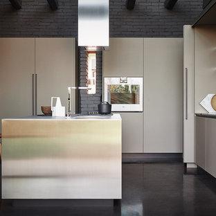 Ejemplo de cocina en L, minimalista, con armarios con paneles lisos, electrodomésticos de acero inoxidable, una isla, puertas de armario beige y suelo de baldosas de porcelana