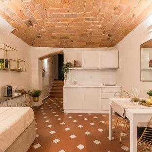Esempio di una piccola cucina mediterranea con lavello da incasso, ante lisce, ante bianche, paraspruzzi bianco, nessuna isola, pavimento marrone e top bianco