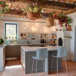Idee per un cucina con isola centrale mediterraneo chiuso con ante lisce, ante grigie, paraspruzzi grigio, paraspruzzi in lastra di pietra, pavimento in terracotta, pavimento arancione, top grigio e travi a vista