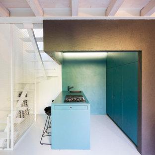 ボローニャの中サイズのコンテンポラリースタイルのおしゃれなキッチン (フラットパネル扉のキャビネット、パネルと同色の調理設備、青いキッチンカウンター、木材カウンター、グレーの床、ドロップインシンク、ターコイズのキャビネット、青いキッチンパネル) の写真