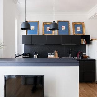 Foto di una cucina parallela moderna con ante lisce, ante nere, paraspruzzi nero, penisola, top nero, lavello da incasso, elettrodomestici bianchi e parquet chiaro