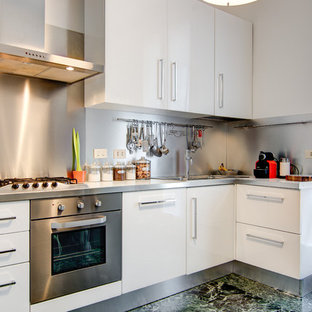 Design ideas for a small contemporary u-shaped open plan kitchen in Milan with an undermount sink, flat-panel cabinets, white cabinets, metal splashback, stainless steel appliances, painted wood floors, no island, beige floor and beige benchtop.