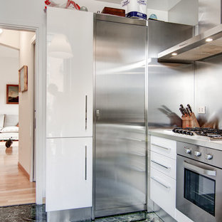Design ideas for a mid-sized contemporary u-shaped open plan kitchen in Milan with an undermount sink, flat-panel cabinets, white cabinets, metal splashback, stainless steel appliances, marble floors, no island, green floor and beige benchtop.