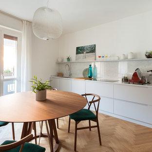 Mittelgroße Moderne Wohnküche in L-Form mit Unterbauwaschbecken, grauen Schränken, Marmor-Arbeitsplatte, Küchenrückwand in Weiß, Rückwand aus Marmor, schwarzen Elektrogeräten, gebeiztem Holzboden und weißer Arbeitsplatte in Mailand