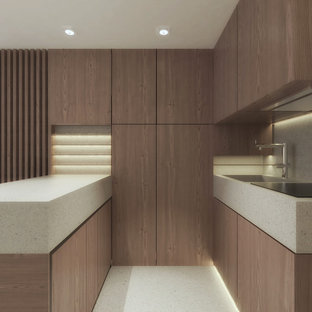 Small contemporary u-shaped open plan kitchen in Rome with an integrated sink, beaded inset cabinets, light wood cabinets, terrazzo benchtops, grey splashback, porcelain splashback, stainless steel appliances, terrazzo floors, with island, grey floor and grey benchtop.