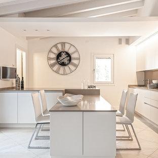 Idee per una grande cucina minimal con ante lisce, ante bianche, top in superficie solida, paraspruzzi beige e una penisola
