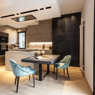 Ispirazione per una grande cucina minimal con ante lisce, top in superficie solida, elettrodomestici in acciaio inossidabile, ante nere, parquet chiaro e 2 o più isole