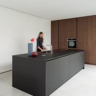 Esempio di un cucina con isola centrale moderno con lavello a vasca singola, ante lisce, ante in legno bruno, elettrodomestici neri, pavimento grigio e top nero