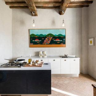 Ejemplo de cocina minimalista con fregadero encastrado, armarios con paneles lisos, puertas de armario blancas, suelo de ladrillo y una isla