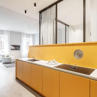 Foto de cocina comedor lineal, minimalista, sin isla, con fregadero bajoencimera, armarios con paneles lisos, puertas de armario amarillas, salpicadero amarillo, suelo de madera clara, encimeras blancas y suelo beige