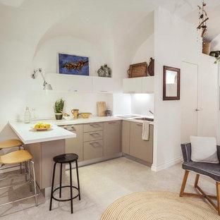 Ispirazione per una cucina costiera con lavello da incasso, ante lisce, ante beige, pavimento in gres porcellanato, pavimento beige e top bianco