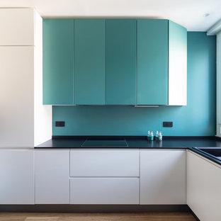 Cette photo montre une cuisine tendance en L avec un évier 2 bacs, un placard à porte plane, des portes de placard turquoises, une crédence bleue, un électroménager en acier inoxydable, un sol en bois clair, aucun îlot, un sol beige et un plan de travail noir.