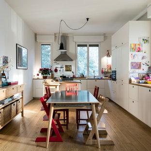 Idee per una grande cucina a L scandinava con ante lisce, top in legno, isola, ante bianche e parquet chiaro