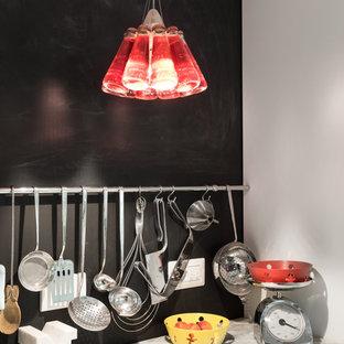 ローマのエクレクティックスタイルのおしゃれなキッチン (フラットパネル扉のキャビネット、白いキャビネット、大理石カウンター、黒いキッチンパネル、白い調理設備、グレーのキッチンカウンター) の写真