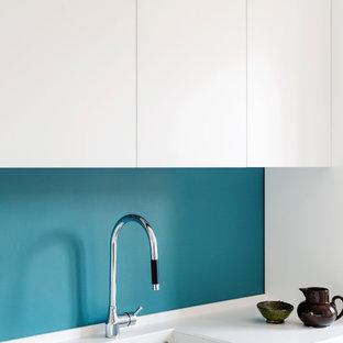 ミラノの中サイズのコンテンポラリースタイルのおしゃれなキッチン (一体型シンク、フラットパネル扉のキャビネット、白いキャビネット、人工大理石カウンター、青いキッチンパネル、黒い調理設備、無垢フローリング、白いキッチンカウンター) の写真