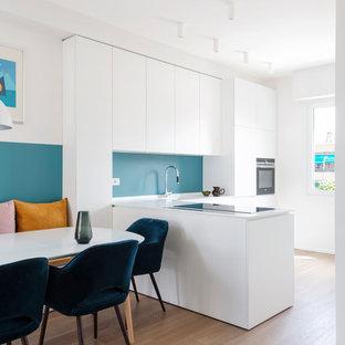 Foto di una cucina minimal di medie dimensioni con lavello integrato, ante lisce, ante bianche, top in superficie solida, paraspruzzi blu, elettrodomestici neri, pavimento in legno massello medio, penisola, top bianco e pavimento marrone