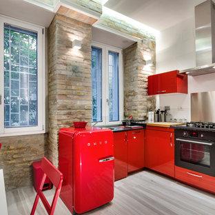 Cette photo montre une cuisine américaine tendance en L de taille moyenne avec un placard à porte plane, des portes de placard rouges, une crédence métallisée, une crédence en dalle métallique, un électroménager noir et un sol en bois brun.
