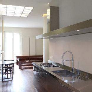 ミラノの小さいコンテンポラリースタイルのおしゃれなキッチン (一体型シンク、ステンレスキャビネット、ステンレスカウンター、シルバーの調理設備、無垢フローリング、赤い床) の写真