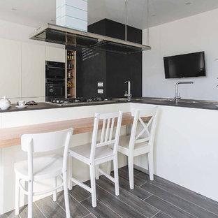Foto på ett mellanstort funkis kök, med en integrerad diskho, släta luckor, rostfria vitvaror, laminatgolv, flera köksöar och grått golv