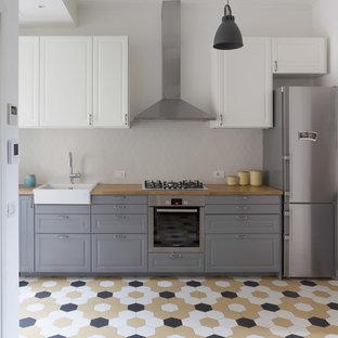 Bild på ett mellanstort skandinaviskt linjärt kök med öppen planlösning, med en enkel diskho, grå skåp, träbänkskiva, stänkskydd i keramik, rostfria vitvaror, klinkergolv i keramik, flerfärgat golv, luckor med upphöjd panel och grått stänkskydd