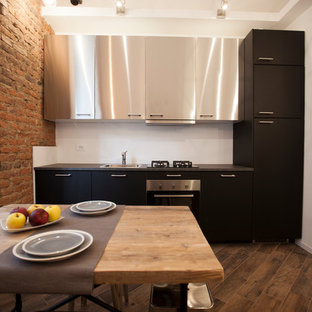 Mid-sized industrial single-wall open plan kitchen in Milan with a drop-in sink, stainless steel cabinets, stainless steel appliances, porcelain floors, no island, brown floor and flat-panel cabinets.