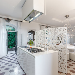 Esempio di una cucina minimal con lavello da incasso, ante lisce, ante bianche, pavimento marrone, top bianco e isola