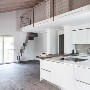 Imagen de cocina en U, contemporánea, con puertas de armario blancas, salpicadero verde, una isla, suelo gris, encimeras blancas, fregadero encastrado y armarios con paneles lisos