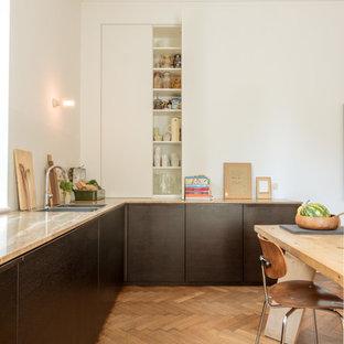 Esempio di una cucina scandinava con lavello a doppia vasca, ante lisce, ante nere, paraspruzzi bianco, pavimento in legno massello medio, pavimento marrone e top marrone