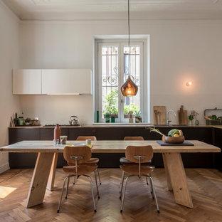 Große Moderne Wohnküche ohne Insel in L-Form mit hellbraunen Holzschränken, Marmor-Arbeitsplatte, Küchenrückwand in Weiß, braunem Holzboden und flächenbündigen Schrankfronten