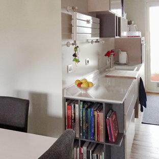 ミラノの小さいコンテンポラリースタイルのおしゃれなキッチン (シングルシンク、インセット扉のキャビネット、ベージュのキャビネット、オニキスカウンター、ベージュキッチンパネル、レンガのキッチンパネル、パネルと同色の調理設備、無垢フローリング、アイランドなし、マルチカラーの床) の写真