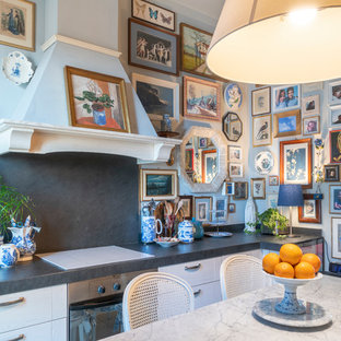 Inspiration for a mid-sized eclectic single-wall separate kitchen in Venice with a drop-in sink, raised-panel cabinets, white cabinets, marble benchtops, multi-coloured splashback, slate splashback, white appliances, porcelain floors, grey floor and black benchtop.