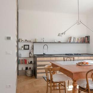 Foto di una cucina contemporanea con lavello sottopiano, ante lisce, ante in legno chiaro, paraspruzzi bianco, pavimento in legno massello medio, nessuna isola, pavimento marrone e top grigio