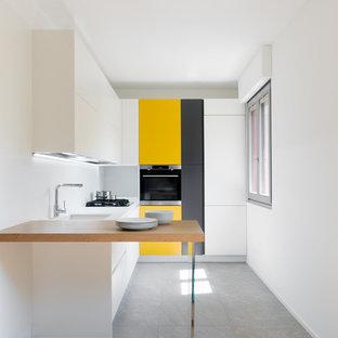Imagen de cocina contemporánea con fregadero bajoencimera, armarios con paneles lisos, puertas de armario amarillas, salpicadero blanco, electrodomésticos de acero inoxidable, península, suelo gris y encimeras blancas