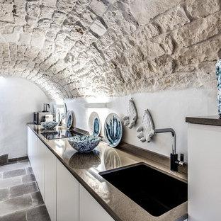 Idee per una cucina lineare mediterranea chiusa con lavello sottopiano, ante lisce, ante bianche, nessuna isola, pavimento grigio e top grigio
