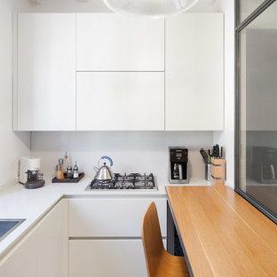 Foto di una cucina ad U minimal chiusa con lavello da incasso, ante lisce, ante bianche, penisola e pavimento bianco