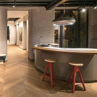 Esempio di un cucina con isola centrale design con lavello a doppia vasca, ante grigie, parquet chiaro e pavimento marrone