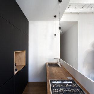 Foto di una cucina a corridoio design di medie dimensioni con lavello da incasso, ante lisce, ante nere, elettrodomestici in acciaio inossidabile e parquet scuro