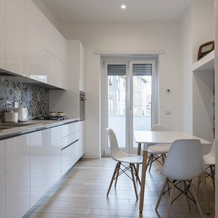 Immagine di una cucina lineare contemporanea chiusa con lavello a doppia vasca, ante lisce, ante bianche, paraspruzzi multicolore, elettrodomestici in acciaio inossidabile, parquet chiaro, nessuna isola, pavimento beige e top bianco