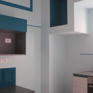 Foto de cocina en U, contemporánea, pequeña, abierta, con fregadero bajoencimera, armarios con paneles lisos, puertas de armario grises, encimera de cuarzo compacto, electrodomésticos de acero inoxidable, suelo de madera clara, península y encimeras turquesas