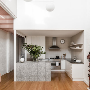 Inspiration for an industrial l-shaped eat-in kitchen in Melbourne with flat-panel cabinets, white cabinets, stainless steel benchtops, white splashback, stainless steel appliances, medium hardwood floors, a peninsula and brown floor.