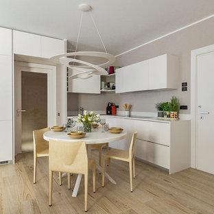 Immagine di una cucina design di medie dimensioni con ante lisce, ante bianche, top in superficie solida, elettrodomestici in acciaio inossidabile, parquet chiaro, nessuna isola, top bianco e pavimento beige