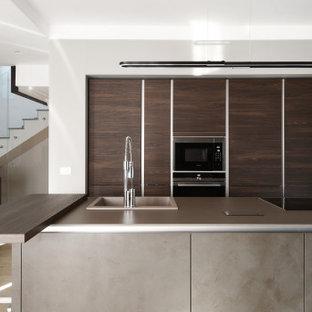 Idee per una cucina parallela contemporanea di medie dimensioni con lavello da incasso, ante lisce, ante in legno scuro, isola, pavimento beige e top grigio