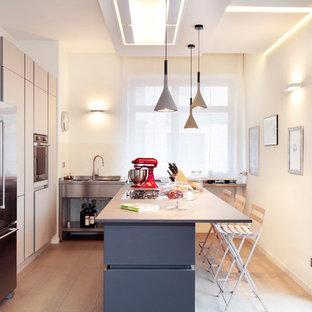 Immagine di una cucina a L contemporanea con lavello integrato, ante lisce, ante beige, elettrodomestici in acciaio inossidabile, un'isola e pavimento beige