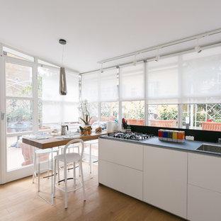 Idee per una cucina abitabile minimal con lavello a doppia vasca, ante lisce, ante bianche, pavimento in legno massello medio, pavimento marrone e top nero
