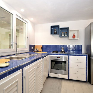 This is an example of a small modern l-shaped open plan kitchen in Other with a drop-in sink, louvered cabinets, white cabinets, tile benchtops, blue splashback, ceramic splashback, stainless steel appliances, porcelain floors, no island, white floor and blue benchtop.