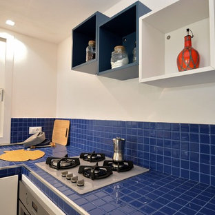 Small modern l-shaped open plan kitchen in Other with a drop-in sink, louvered cabinets, white cabinets, tile benchtops, blue splashback, ceramic splashback, stainless steel appliances, porcelain floors, no island, white floor and blue benchtop.