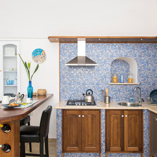 Photo of a mediterranean l-shaped kitchen in Other with a single-bowl sink, raised-panel cabinets, medium wood cabinets, multi-coloured splashback, stainless steel appliances, a peninsula and beige benchtop.