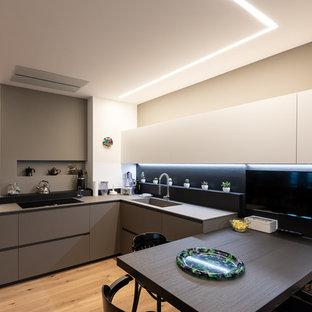Idee per una cucina design con lavello a vasca singola, ante lisce, ante grigie, paraspruzzi nero, parquet chiaro e top grigio